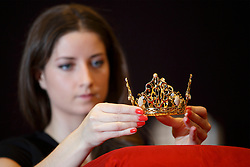 © licensed to London News Pictures. London, UK 29/11/2013. The tiara which was worn by Victoria Beckham at her wedding is shown at a photo call at Bonham, London before it is sold at an auction for estimate of £18,000-£25,000. The tiara is entitled East of Paris and designed by Slim Barrett and it is crafted from 18-carat latticed yellow gold, set with large brilliant-cut diamonds and suspended diamond drops. Photo credit: Tolga Akmen/LNP
