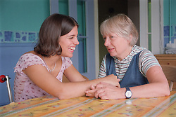 Teenage girl with physical disability sitting at kitchen table in residential respite care home laughing and holding hands with carer,