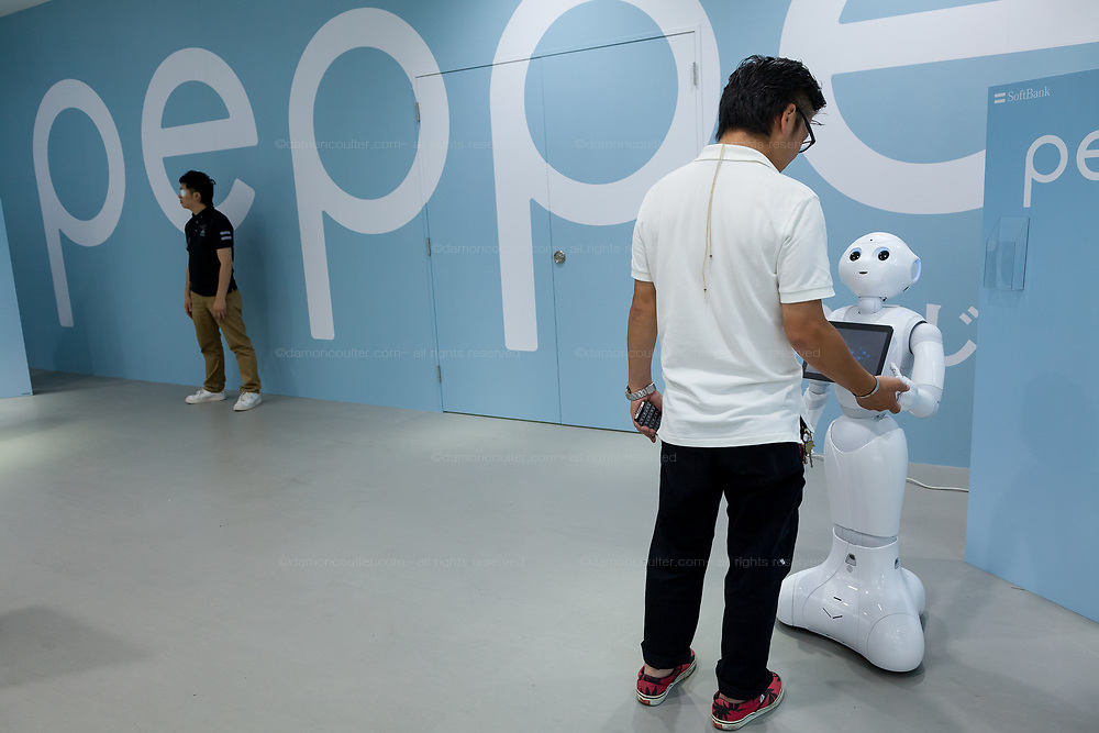 A Japanese man interacts with Softbank's emotional consumer Robot, Pepper on display at the Softbank Store Omotesando, Tokyo, Japan. Friday June 13th 2014. At the end of June 2021 the Softbank company announced it was cutting jobs in its global robotics business and had stopped production of the Pepper robot.
