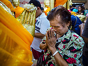31 MAY 2017 - CHACHOENGSAO, THAILAND:  A woman prays after wrapping a statue of the Buddha in orange cloth at Wat Sothon (also spelled Sothorn) in Chachoengsao, Thailand. The temple is one of the largest and most visited in Thailand. People make merit by paying to wrap the Buddha statues in orange robes. The temple is most famous because people leave hard boiled eggs as an offering at the temple. They ask for business success or children and leave hundreds of hard boiled eggs.     PHOTO BY JACK KURTZ