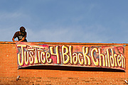 "20 AUGUST 2020 - DES MOINES, IOWA: A member of the Black Liberation Movement hangs a banner calling for justice for Black children during a vigil for missing Black children. About 150 people, members of and supporters of Des Moines Black Liberation Movement (which used to be known as Black Lives Matter) marched through a residential neighborhood of Des Moines Thursday night demanding justice for Black children. The march was called to show support for Breasia Terrell and  Abdullahi ""Abdi"" Sharif, two Black children who went missing in Iowa this year. Terrell, a 10 year old girl,  went missing on July 10 and is still missing. Sharif, a teenager, disappeared from a Des Moines shopping mall in January, his body was found in May. Members of BLM said authorities have not adequately investigated the disappearances.     PHOTO BY JACK KURTZ"