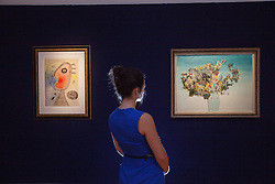 """© licensed to London News Pictures. London, UK 15/06/2012. Joan Miro's """"Femme et oiseau devant le soleil"""" painting (left) expected to be sold for £300.000 - £500.000 and Enrico Donati's """"Fleures Surrealistes"""" painting expected to be sold for £20.000 - £30.000 by Bonhams on 19/06/12. Photo credit: Tolga Akmen/LNP"""