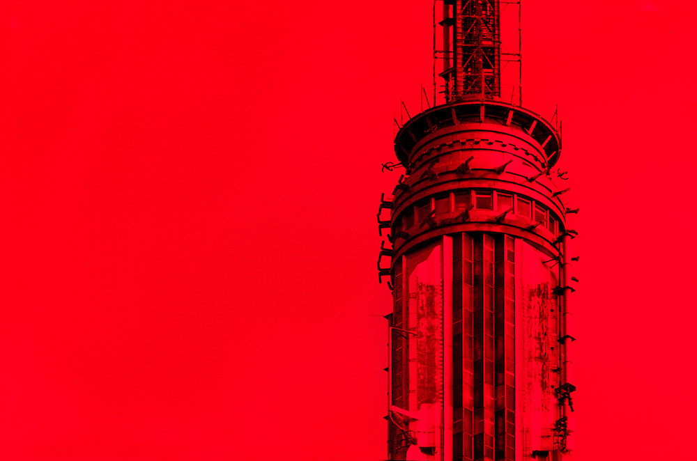 The Empire State Building's Art Deco spire & 102nd floor observatory, photographed through a deep red-orange filter