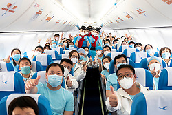 March 17, 2020, Wuhan, China: Medics from north China's Tianjin Municipality gesture for a group photo with cabin staff aboard an airplane at the Wuhan Tianhe International Airport in Wuhan, central China's Hubei Province. The first batch of medics has been scheduled to depart Hubei, once the hard-hit province of the novel coronavirus, on Tuesday, as the epidemic situation has been greatly eased. The 3,675 medical staffers belonging to 41 medical teams from across China have assisted 14 temporary hospitals and seven designated hospitals in Wuhan, the provincial capital and epicenter of the outbreak. (Credit Image: © Xiong Qi/Xinhua via ZUMA Wire)