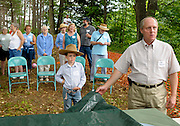 Logan Winny, 7, of Lebanon, left, takes his position in the front row as Mike Schwarz, facilities manager of Lyme Properties, right, waits for the right moment to unveil a scale model of the company's proposed development in West Lebanon, N.H., Sunday, July 19, 2009. West Lebanon residents were shown the model during a promotional picnic on the proposed 38 acre site between Route 10 and the Connecticut River.<br /> Valley News - James M. Patterson