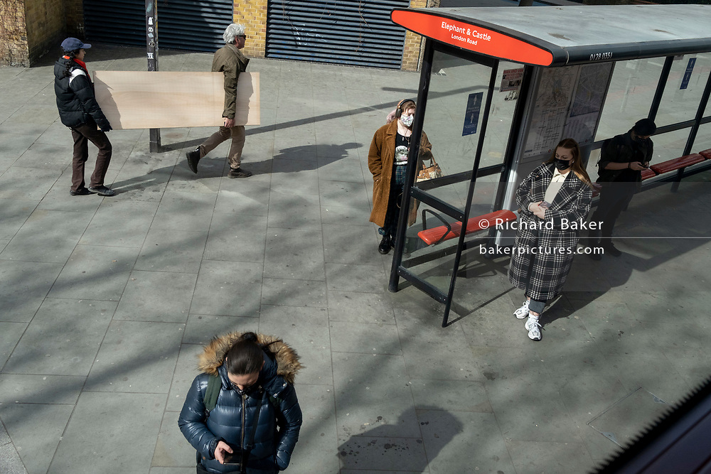A man and woman carry an awkward wooden board along the street at Elephant & Castle, on 9th April 2021, in London, England.