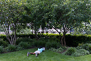 A day after the Covid 'Freedom Day', when social distancing and the wearing of face coverings are no longer mandatory, a man lies on the grass beneath largely empty office premises as the majority of City workers remain working from home, on 21st July 2021, in London, England.