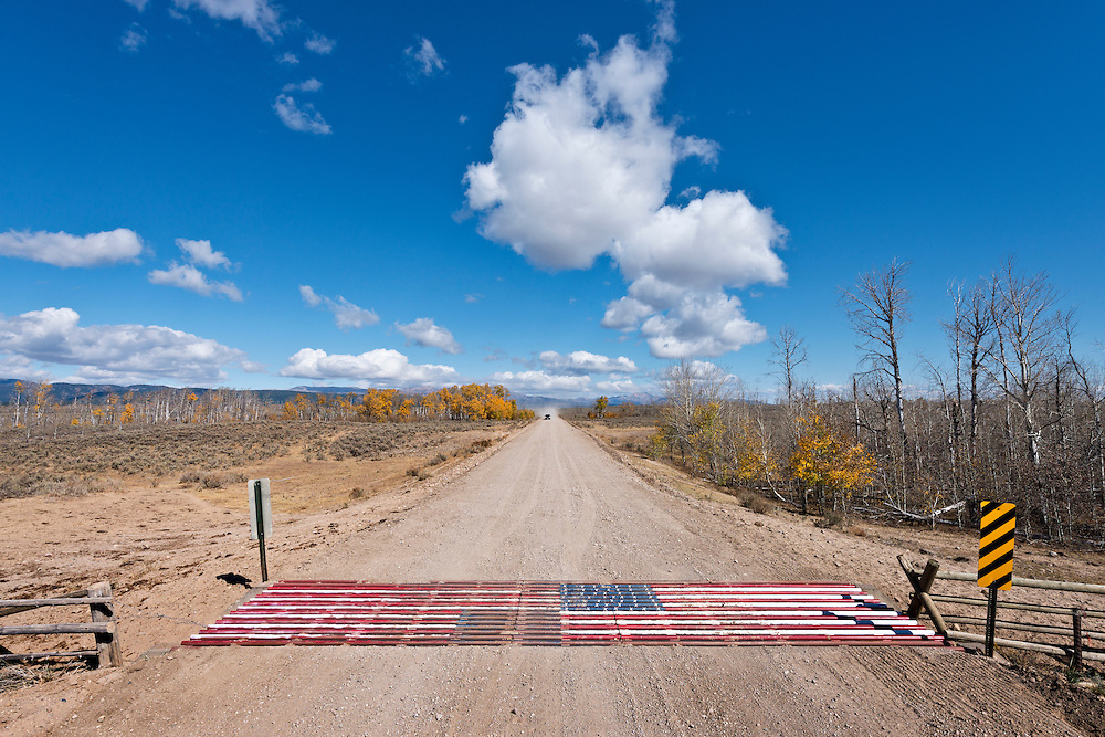 Editions of 17<br /> Patriotic American Flag cattle guard on country road in Eastern Idaho with a few autumn colors still hanging on and a pick-up truck in the distance travel toward cattle guard