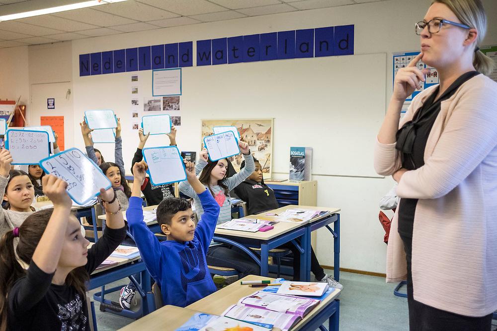 Nederland. Amsterdam, 11-01-2017. Foto: Patrick Post. Leerlingen van Alan Turingschool steken bordjes met de juiste antwoorden erop tijdens de rekenles van Juf Marie-Jose.
