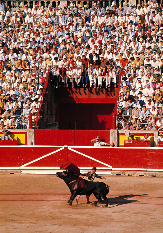 A colorful crowd of spectators fills the stands for a bullfight at the Plaza de Toros in Madrid, Spain.