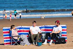 Portobello, Scotland, UK. 3 April 2021. Easter weekend crowds descend on Portobello beach and promenade to make the most of newly relaxed  Covid-19 lockdown travel restrictions and warm sunshine with uninterrupted blue skies. Pic; Picnics were popular on the beach.  Iain Masterton/Alamy Live News