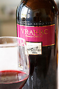 Wine glasses in the tasting room. Bottle of Vranac Vrhunsko Suho Vino red wine. Detail of label with picture of winery building. Vinarija Citluk winery in Citluk near Mostar, part of Hercegovina Vino, Mostar. Federation Bosne i Hercegovine. Bosnia Herzegovina, Europe.