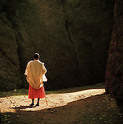 Man standing between the walls of Saint George's Church, Lalibela, Ethiopia.