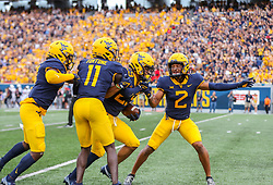 Oct 2, 2021; Morgantown, West Virginia, USA; West Virginia Mountaineers safety Sean Mahone (29) celebrates with teammates following an interception during the first quarter against the Texas Tech Red Raiders at Mountaineer Field at Milan Puskar Stadium. Mandatory Credit: Ben Queen-USA TODAY Sports