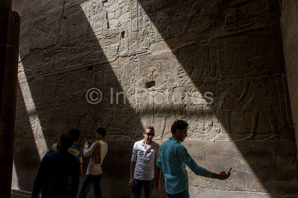 Egyptian tourists take selfies under sunlit hieroglyphs in the dark recesses of the ancient Egyptian Luxor Temple, Nile Valley, Egypt. According to the country's Ministry of Tourism, European visitors to Egypt is down by up to 80% in 2016 from the suspension of flights after the downing of the Russian airliner in Oct 2015. Euro-tourism accounts for 27% of the total flow and in total, tourism accounts for 11.3% of Egypt's GDP. The temple was built by Amenhotep III, completed by Tutankhamun then added to by Rameses II. Towards the rear is a granite shrine dedicated to Alexander the Great and in another part, was a Roman encampment. The temple has been in almost continuous use as a place of worship right up to the present day.