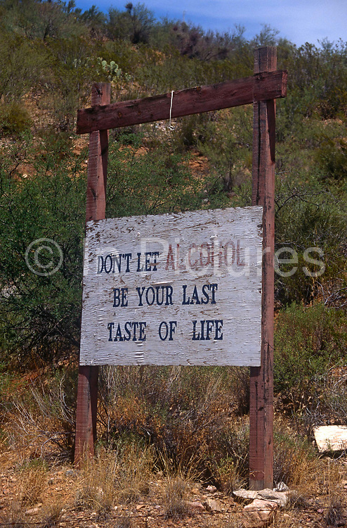 A roadside sign warns local Native Americans of alcohol dependency, on 25th August 1998, at San Carlos Apache Reservation, Arizona, USA.
