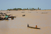 """Tipical """"pinasses"""" canoes navigate in  Mopti's harbor. At the confluence of the Niger and the Bani rivers, between Timbuktu and Ségou, Mopti is the second largest city in Mali, and the hub for commerce and tourism in this west-african landlocked country."""