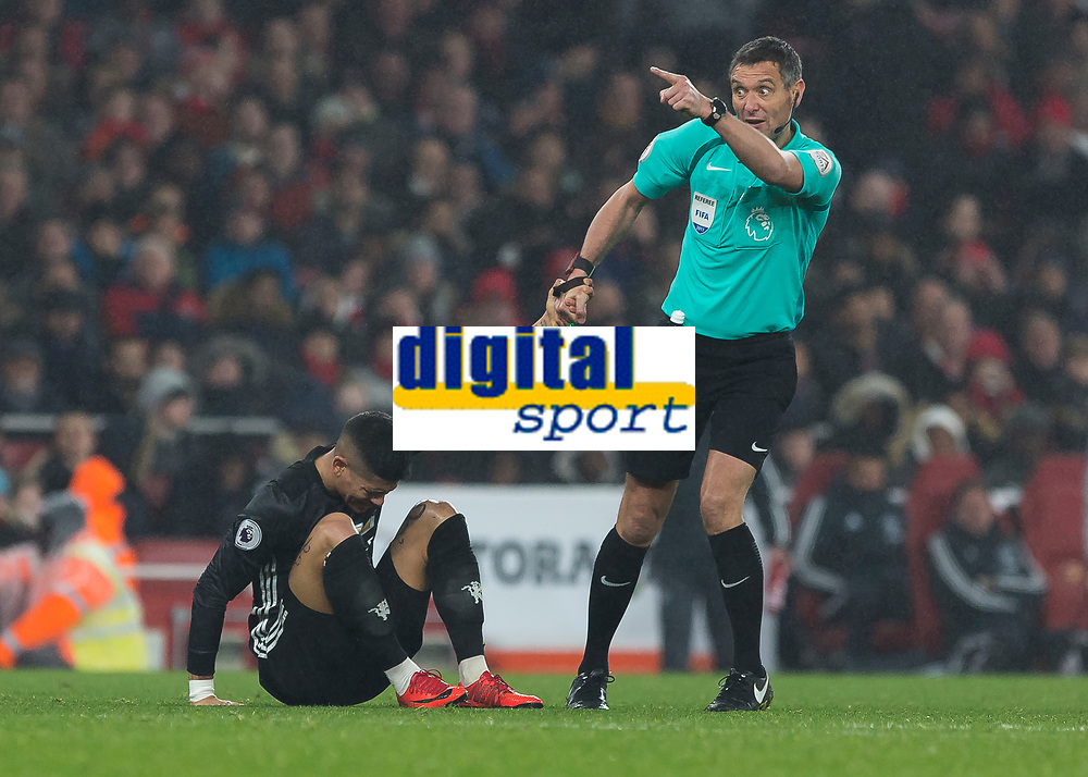 Football - 2017 / 2018 Premier League - Arsenal vs. Manchester United<br /> <br /> Andre Marriner (Referee) pulls up Marcos Rojo (Manchester United) to stop time wasting after he feigns injury at The Emirates.<br /> <br /> COLORSPORT/DANIEL BEARHAM
