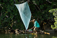 A man from Arawai Village uses a fine net to dip for very small shrimp that are used to make shrimp paste, a major ingredient in Indonesian cooking.  It is the major export from this village.
