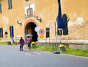 Women walking with umbrellas for shade towards the fort doorway exit in the historic town of Galle, Sri Lanka, Asia