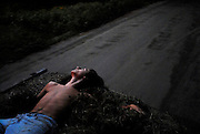 Ethan Descoteau, 17, relaxes in a load of loose hay driven by his mother near their Thetford, Vt., home in September, 2008.