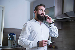 Young man talking on smartphone and drinking coffee in the kitchen, Bavaria, Germany