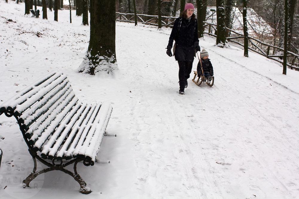 Een vrouw loopt met een kind op de slee door de sneeuw in het Sonsbeekpark in Arnhem.<br /> <br /> A woman is walking with a boy on a sled at the Sonsbeekpark in Arnhem.