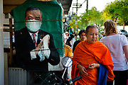 Buddhist monk passing street poster of man wearing hygiene mask, Bangkok, Thailand.