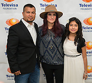 """Telenovela actress Dulce Maria, center, poses for a photograph with parents and students following a Televisa Foundation """"Live the Dream"""" event at Burbank Middle School, December 9, 2013."""