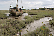 A low-tide landscape of poetry and sentences forming Graveyard of Lost Species, an boat artwork created by by artists and commissioned by Arts Catalyst, at low-tide on the Thames estuary, at Leigh creek, on 10th September 2019, in Leigh-on-Sea, Essex, England. The project celebrates the local tradition of wrecking boats on the salt marsh, its decaying memory of what has changed or passed. The boat is the Souvenir, a 39-foot Thames bawley 1933 which once served the local fish trade in nearby Southend-on-Sea.