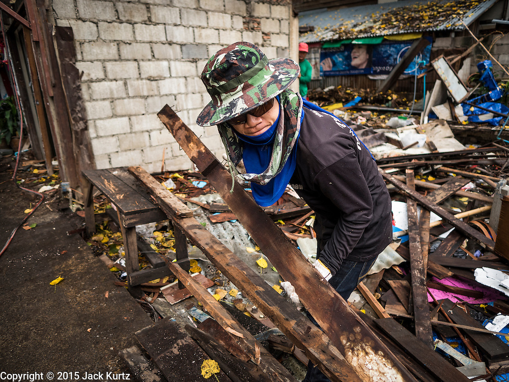 28 SEPTEMBER 2015 - BANGKOK, THAILAND:  A demolition worker tears down a home at Wat Kalayanamit. Fifty-four homes around Wat Kalayanamit, a historic Buddhist temple on the Chao Phraya River in the Thonburi section of Bangkok, are being razed and the residents evicted to make way for new development at the temple. The abbot of the temple said he was evicting the residents, who have lived on the temple grounds for generations, because their homes are unsafe and because he wants to improve the temple grounds. The evictions are a part of a Bangkok trend, especially along the Chao Phraya River and BTS light rail lines. Low income people are being evicted from their long time homes to make way for urban renewal.   PHOTO BY JACK KURTZ