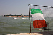 A speedboat passes the Italian flag on Venice's Canale delle Fondamenta Nuove in the Cannaregio district. The flag is otherwise known as the Tricolore, three colours used as a symbol of Italy. The inshore sea is the Canale delle Fondamenta Nuove that separates Cannaregio from the island of Murano in the distance.