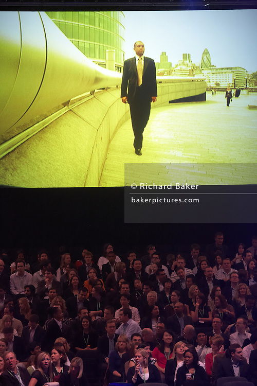 Employees watch motivational film at their corporate rally day, held for 3,000 UK staff at Excel