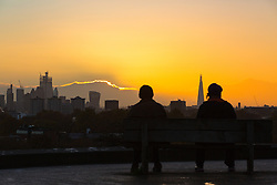 Friends await the moment the sun appears from behind distant clouds as day breaks over London's skyline, seen from Primrose Hill, to the north of the city. London, November 13 2018.