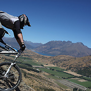 Joseph Nation from Christchurch in action during the New Zealand South Island Downhill Cup Mountain Bike series held on The Remarkables face with a stunning backdrop of the Wakatipu Basin. 150 riders took part in the two day event. Queenstown, Otago, New Zealand. 9th January 2012. Photo Tim Clayton