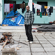 A refugee from Syria is trying to warm by an open fire in the abandoned army barracks next to to Idomeni railway station. <br /> <br /> Thousands of refugees are stranded in Idomeni unable to cross the border. The facilities here are stretched to the limit and the conditions are appalling. It's raining, it's cold there is mud everywhere and there is no hope that the border will open anytime soon.