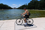 WASHINGTON - JUNE 30, 2019: A bicyclist rides near the Lincoln Memorial Reflecting Pool on June 30, 2019, in Washington, D.C.