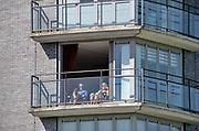 Nederland, Nijmegen, 5-4-2020 Een echtpaar zit in de zon op hun balkon tijdens de coronacrisis . Mensen meoet ook met het mooie weer zoveel mogelijk thuis of binnen blijven . Het is lekker voorjaarsweer . Foto: Flip Franssen