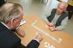 Volunteer playing dominoes with service user at a resource for people with physical and sensory impairment.