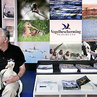Nederland, Zeist, 30 oktober 2009..Op vrijdag 30 en zaterdag 31 oktober organiseert Vogelbescherming Nederland de Tuinvogeldagen in en om haar pand in Zeist..Tijdens de Tuinvogeldagen wordt er doorlopend informatie gegeven over het voeren van vogels en hoe u uw tuin vogelvriendelijk kunt maken..Verder wordt er doorlopend informatie gegeven over het werk van Vogelbescherming en er zijn lezingen over tuin- en stadsvogels. Op het centrale plein kunt u onder het genot van een kopje koffie de Tv-serie 'Een tuin vol vogels' volgen. Voor kinderen liggen er grappige vogelplaten om in te kleuren en kunnen ze proberen om als een vogel met een pincet smarties uit een voedersilo te pakken..Op de foto: Standhouder van Vogelbescherming Nederland met Albatrossen op zijn knieen wacht op bezoekers..Netherlands Bird Protection organizes the Garden Bird Days and gives information to people ito attract more birds into their gardens.