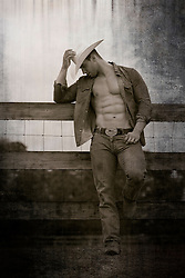 cowboy with an open shirt leaning on a wooden fence on a ranch