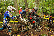 Bill Dragoo rides the R1200GS down into a creek while Briena Thompson and Brad ? steady the bike.