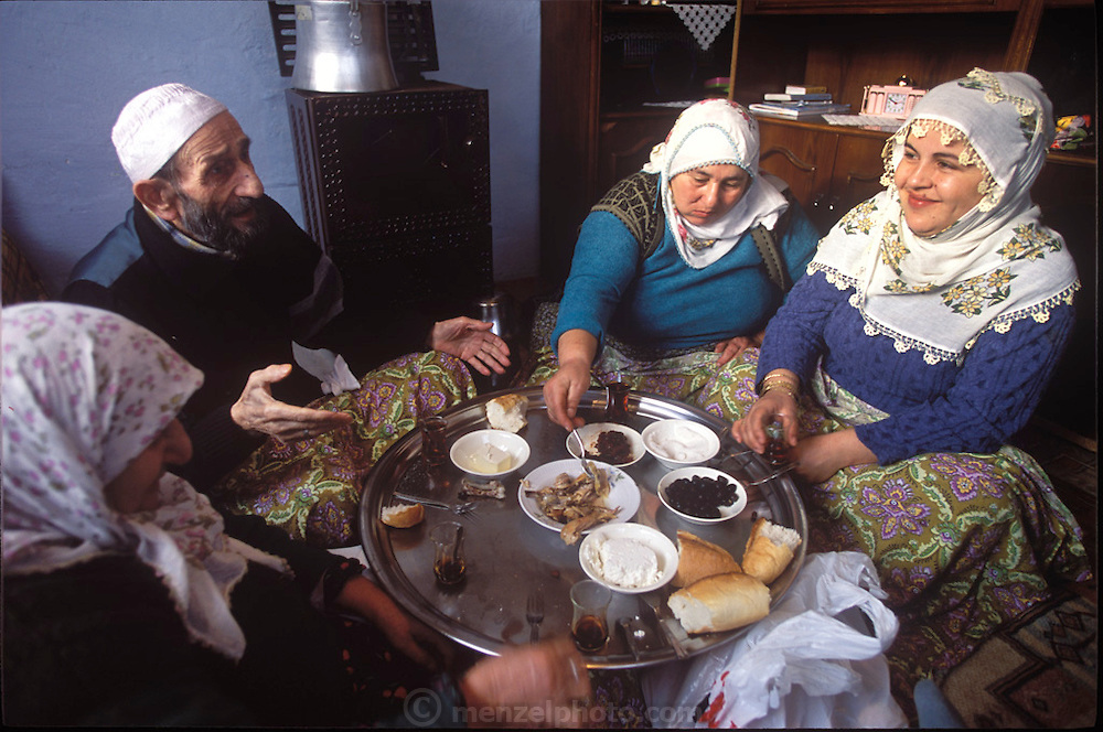 (MODEL RELEASED IMAGE). In the Golden Horn area of Istanbul, Turkey, the Çinar family gathers on the floor of their small living room to share their morning meal: feta cheese, olives, leftover chicken, bread, rose jam, and sweet, strong tea. (Supporting image from the project Hungry Planet: What the World Eats.)