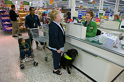 Woman with a visual impairment and her Guide dog at the checkout desk in a supermarket,