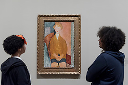 """© Licensed to London News Pictures. 21/11/2017. London, UK.  Staff members view """"Boy in Short Pants"""", 1918.  Preview of """"Modigliani"""", the most comprehensive exhibition of works by Amedeo Modigliani ever held in the UK.  On display are iconic portraits, sculptures and 12 nudes, the largest group ever shown in the UK.  The show runs 23 November to 2 April 2018.  Photo credit: Stephen Chung/LNP"""
