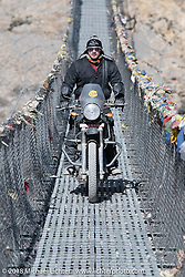 Chris Shelby riding across a narrow suspension bridge over the Kali Gandaki River on day-6 of our Himalayan Heroes adventure riding from Muktinath to Tatopani, Nepal. Sunday, November 11, 2018. Photography ©2018 Michael Lichter.