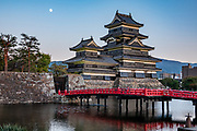 "Built 1592-1614, Matsumoto Castle and its red bridge reflect in the moat during moonrise in Matsumoto, Nagano Prefecture, Japan. Matsumoto Castle is a ""hirajiro"" - a castle built on plains rather than on a hill or mountain, in Matsumoto. Matsumotojo's main castle keep and its smaller, second donjon were built from 1592 to 1614, well-fortified as peace was not yet fully achieved at the time. In 1635, when military threats had ceased, a third, barely defended turret and another for moon viewing were added to the castle. Interesting features of the castle include steep wooden stairs, openings to drop stones onto invaders, openings for archers, as well as an observation deck at the top, sixth floor of the main keep with views over the Matsumoto city."