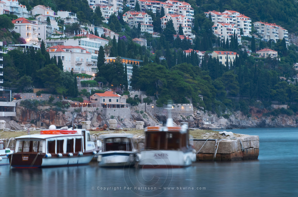Tourist and charter boats moored in the old harbour against a background of houses on the hill side in evening blue light Dubrovnik, old city. Dalmatian Coast, Croatia, Europe.