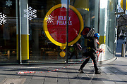 A workman from a nearby contruction site carries traffic cones and tape past the M&M store in Leicester Square in the West End, on 1st December 2020, in London, England.