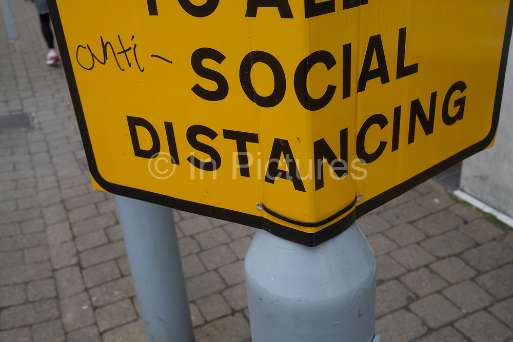 Anti-vaxxer defaced social distancing sign during the coronavirus or Covid-19 pandemic reads anti-social distancing on 9th June 2021 in Hereford, United Kingdom. After months of lockdown, and easing beginning, social distancing measure and signage are still in place, much to the consternation of local rural anti-vaccine supporters. Among vaccine hesitancy are groups known as anti-vaxxers or anti vax, who are generally against vaccination.